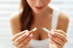 Χέρι γυναικών που παρουσιάζει σπασμένο τσιγάρο τρόπος ζωής ανθυγειινός Στοκ Εικόνες