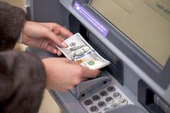 Χέρι γυναικών που παρουσιάζει τραπεζογραμμάτια δολαρίων μπροστά από το ATM Στοκ Εικόνες
