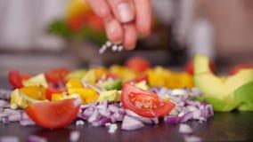 Χέρι γυναικών που προσθέτει το μεγάλο άλας σιταριού στο μίγμα λαχανικών - σε αργή κίνηση απόθεμα βίντεο