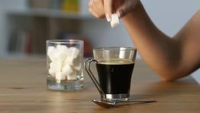 Χέρι γυναικών που ρίχνει τον κύβο ζάχαρης σε μια κούπα καφέ απόθεμα βίντεο