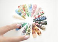 Χέρι γυναικών που τακτοποιεί τα πλαστά καρφιά Στοκ Εικόνες