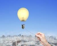 Χέρι γυναικών που τραβά συνδεδεμένο το σχοινί lightbulb μπαλόνι ζεστού αέρα Στοκ Φωτογραφία
