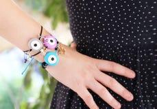 Χέρι γυναικών που φορά τα μοντέρνα κακά βραχιόλια ματιών Στοκ εικόνα με δικαίωμα ελεύθερης χρήσης
