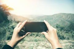 Χέρι γυναικών που χρησιμοποιεί την κινητή τηλεφωνική φωτογραφία Φύση βουνών Στοκ φωτογραφία με δικαίωμα ελεύθερης χρήσης