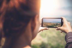Χέρι γυναικών που χρησιμοποιεί την κινητή τηλεφωνική φωτογραφία Φύση βουνών Στοκ Εικόνες