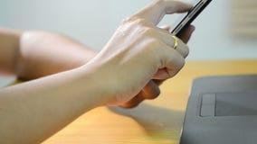 Χέρι γυναικών που χρησιμοποιεί το έξυπνο τηλέφωνο απόθεμα βίντεο