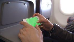 Χέρι γυναικών που χρησιμοποιεί το τηλέφωνο κυττάρων στο αεροπλάνο φιλμ μικρού μήκους