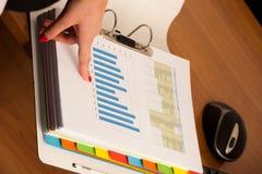 Χέρι γυναικών σε μια πρώτη σελίδα ενός επιχειρησιακού φακέλλου που ελέγχει τα στοιχεία Στοκ Εικόνες