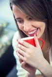 Χέρι γυναικών ` s που κρατά ένα κόκκινο φλιτζάνι του καφέ Με ένα όμορφο winte στοκ φωτογραφίες με δικαίωμα ελεύθερης χρήσης
