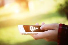 Χέρι γυναικών ` s που κρατά το κινητό έξυπνο τηλέφωνο με το wifi που συνδέει το SCR Στοκ Φωτογραφία