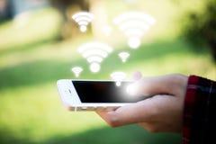 Χέρι γυναικών ` s που κρατά το κινητό έξυπνο τηλέφωνο με το wifi που συνδέει το SCR Στοκ εικόνες με δικαίωμα ελεύθερης χρήσης