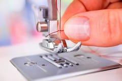 Χέρι γυναικών ` s που περνά κλωστή στη βελόνα ράβοντας μηχανών στοκ εικόνες