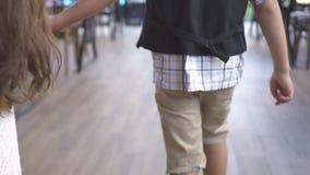 Χέρι εκμετάλλευσης μικρών παιδιών και κοριτσιών και περπάτημα μέσα στον καφέ Πίσω μικρό παιδί άποψης που κρατά στο μικρό κορίτσι  απόθεμα βίντεο