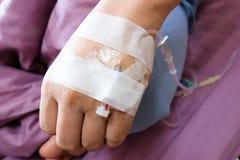 Χέρι ενός ατόμου που αρρωσταίνουν και όντας επεξεργασία από την έγχυση υφάλμυρου νερού Ι Β & x28 intravenous& x29  Ρευστός σωλήνα στοκ φωτογραφίες