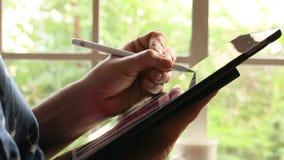 Χέρι ενός γραφικού σχεδιαστή που επισύρει την προσοχή στην ψηφιακή ταμπλέτα απόθεμα βίντεο