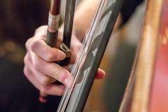 Χέρι ενός κοριτσιού που παίζει μια κινηματογράφηση σε πρώτο πλάνο βιολοντσέλων contrabass Στοκ φωτογραφία με δικαίωμα ελεύθερης χρήσης