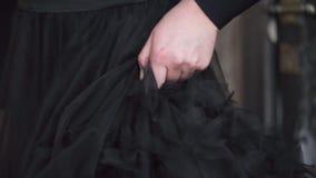 Χέρι ενός κοριτσιού σχετικά με το φόρεμά της απόθεμα βίντεο