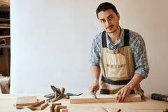 Χέρι ενός ξυλουργού που παίρνει τη μέτρηση μιας ξύλινης σανίδας στοκ φωτογραφία
