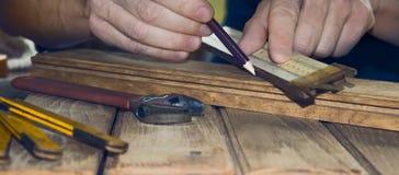 Χέρι ενός ξυλουργού που παίρνει τη μέτρηση ενός ξύλινου στοκ φωτογραφία