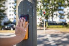 Χέρι ενός παιδιού στο χωρητικό κουμπί ώθησης ενός για τους πεζούς TR στοκ φωτογραφία με δικαίωμα ελεύθερης χρήσης