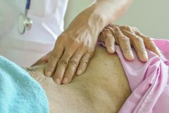 Χέρι ενός στομαχιού ελέγχου γιατρών στοκ εικόνες