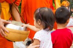 Χέρι ενώ οι τεθειμένες προσφορές τροφίμων στις ελεημοσύνες ενός βουδιστικού μοναχού κυλούν φ Στοκ Φωτογραφία