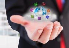 Χέρι επιχειρηματιών με τα εικονίδια εφαρμογής γύρω από τη γη με το σύννεφο πίσω Στοκ εικόνες με δικαίωμα ελεύθερης χρήσης