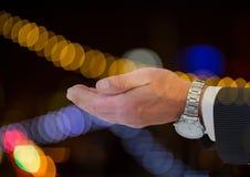 Χέρι επιχειρηματιών με το πλούσιο ρολόι με το λαμπιρίζοντας ελαφρύ υπόβαθρο bokeh Στοκ εικόνα με δικαίωμα ελεύθερης χρήσης