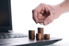 Χέρι επιχειρηματιών που βάζει το χρυσό νόμισμα στο σωρό των νομισμάτων Στοκ Φωτογραφία