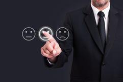Χέρι επιχειρηματιών που δείχνει το εικονίδιο προσώπου smiley από την οθόνη Στοκ Εικόνες