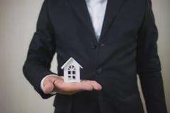 Χέρι επιχειρηματιών που κρατά τον πρότυπο Λευκό Οίκο Η επένδυση ιδιοκτησίας και η οικονομική έννοια υποθηκών σπιτιών, σπίτι προστ στοκ φωτογραφίες με δικαίωμα ελεύθερης χρήσης