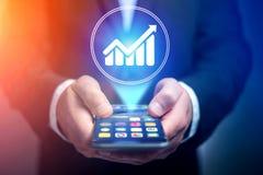 Χέρι επιχειρηματιών που κρατά το κινητό τηλέφωνο με το εικονίδιο διαγραμμάτων Στοκ εικόνες με δικαίωμα ελεύθερης χρήσης