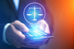 Χέρι επιχειρηματιών που κρατά το κινητό τηλέφωνο με το εικονίδιο δικαιοσύνης Στοκ Εικόνες