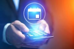 Χέρι επιχειρηματιών που κρατά το κινητό τηλέφωνο με το ημερολογιακό εικονίδιο Στοκ φωτογραφία με δικαίωμα ελεύθερης χρήσης
