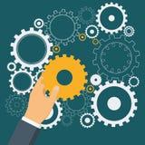 Χέρι επιχειρηματιών ` s που βάζει το χρυσό εργαλείο cogwheel στο μηχανισμό απεικόνιση αποθεμάτων