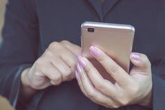 Χέρι επιχειρησιακών γυναικών που κρατά το κινητό τηλέφωνο συνδέοντας με Διαδίκτυο Στοκ Εικόνες