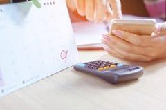 Χέρι επιχειρησιακών γυναικών που υπολογίζει την ετήσια έκθεση λογιστικής της εσόδων και εξόδων με το έξυπνο τηλέφωνό της Στοκ φωτογραφία με δικαίωμα ελεύθερης χρήσης
