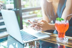 Χέρι επιχειρησιακών γυναικών χρησιμοποιώντας ένα τηλέφωνο κυττάρων και εργαζόμενος με ένα lap-top Στοκ Φωτογραφίες