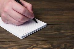 Χέρι και ένα σημειωματάριο με μια μαύρη μάνδρα ballpoint Στοκ Εικόνα