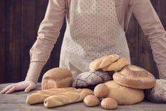 Χέρι και διαφορετικοί τύποι ψωμιών στο ξύλινο υπόβαθρο στοκ φωτογραφία