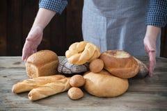 Χέρι και διαφορετικοί τύποι ψωμιών στο ξύλινο υπόβαθρο στοκ εικόνα με δικαίωμα ελεύθερης χρήσης