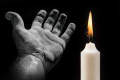 Χέρι και κερί σε ένα μαύρο υπόβαθρο σχετικά με το θέμα του θανάτου στοκ εικόνα