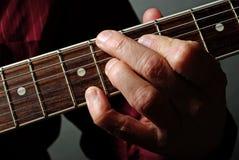 Χέρι και κιθάρα κιθαριστών Ψαρευμένος παίζοντας μια χορδή κιθάρων στοκ εικόνες