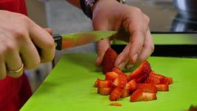 Χέρι και μαχαίρι αρχιμαγείρων που τεμαχίζουν τη φρέσκια φράουλα στον τέμνοντα πίνακα φιλμ μικρού μήκους