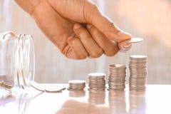 Χέρι και σωρός των νομισμάτων Στοκ Φωτογραφίες