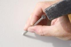 Χέρι κινηματογραφήσεων σε πρώτο πλάνο με το καρφί και σφυρί στον τοίχο Στοκ φωτογραφία με δικαίωμα ελεύθερης χρήσης
