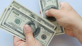 Χέρι κινηματογραφήσεων σε πρώτο πλάνο που μετρά τους λογαριασμούς 100 αμερικανικών δολαρίων φιλμ μικρού μήκους
