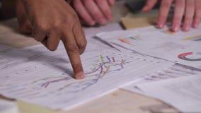 Χέρι κινηματογραφήσεων σε πρώτο πλάνο του businesspeople με την αναθεώρηση οικονομικές στατιστικές φιλμ μικρού μήκους