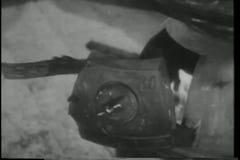 Χέρι κινηματογραφήσεων σε πρώτο πλάνο που τείνει την πυρκαγιά στην ξύλινη καίγοντας σόμπα φιλμ μικρού μήκους