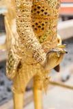Χέρι κινηματογραφήσεων σε πρώτο πλάνο του χρυσού αγάλματος Kinnara Στοκ Φωτογραφίες